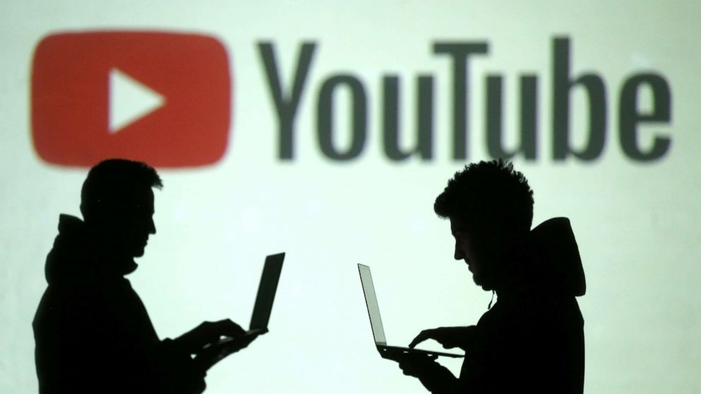 Silhouettes of mobile device users are seen next to a screen projection of Youtube logo, March 28, 2018.