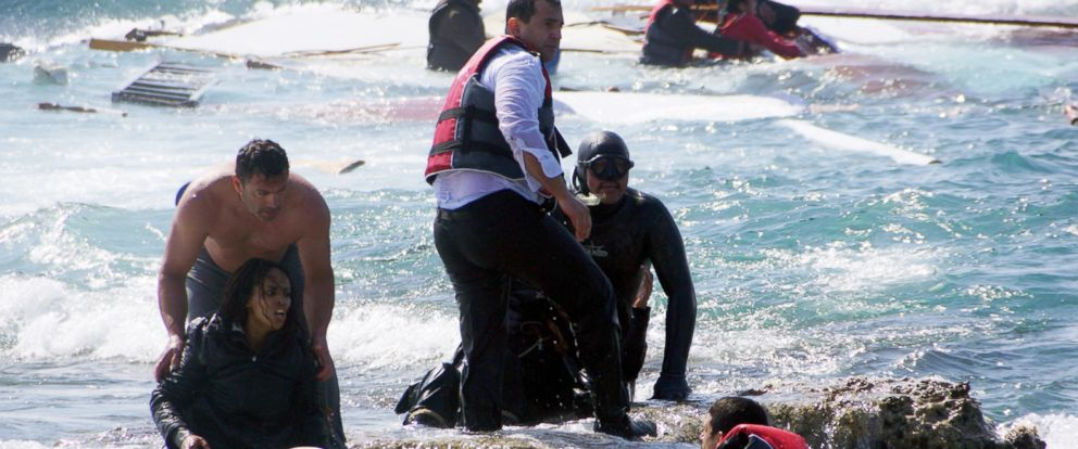 PHOTO: A man rescues an migrant from the Aegean sea, in the eastern island of Rhodes, April 20, 2015