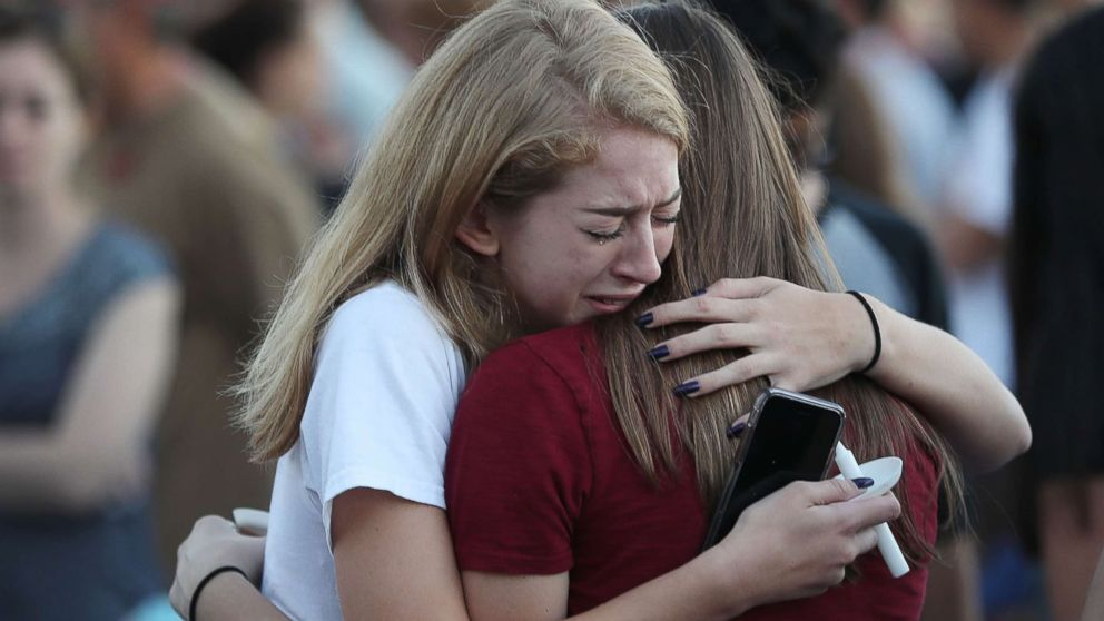 People hug as they attend a candlelit memorial service for the victims of the shooting at Marjory Stoneman Douglas High School that killed 17 people, Feb. 15, 2018, in Parkland, Fla.