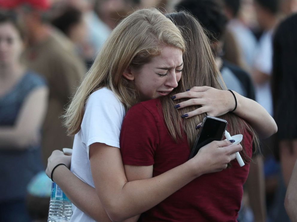 PHOTO: People hug as they attend a candlelit memorial service for the victims of the shooting at Marjory Stoneman Douglas High School that killed 17 people, Feb. 15, 2018, in Parkland, Fla.