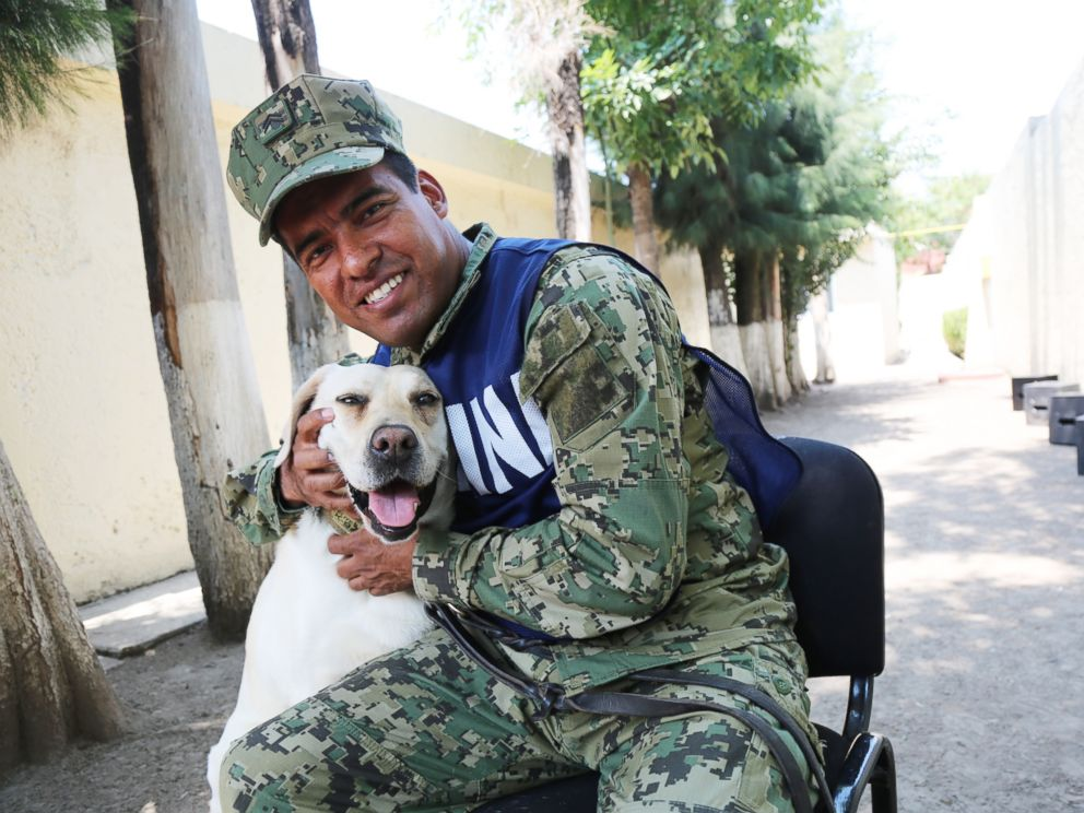 PHOTO: Israel Arauz Salinas hugs rescue dog Frida, who is his partner at the Mexican Navy Canine Unit.