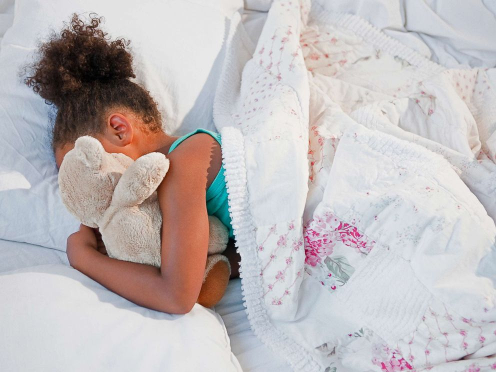 PHOTO: A girl sleeps with a teddy bear in this undated stock photo.