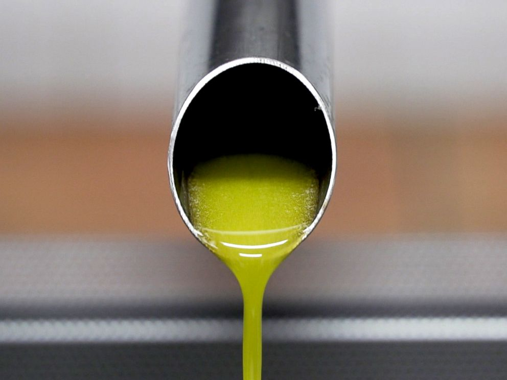 PHOTO: Freshly crushed olive oil is emerging from a small press prior to bottling.