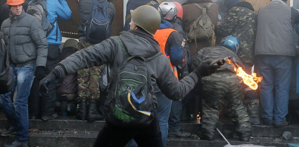 PHOTO: An anti-government protester, center, throw a Molotov cocktail during clashes with riot police in Kievs Independence Square, the epicenter of the countrys current unrest, Kiev, Ukraine, Wednesday, Feb. 19, 2014.