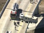 WATCH:  Scary scene as camper dangles from interstate overpass