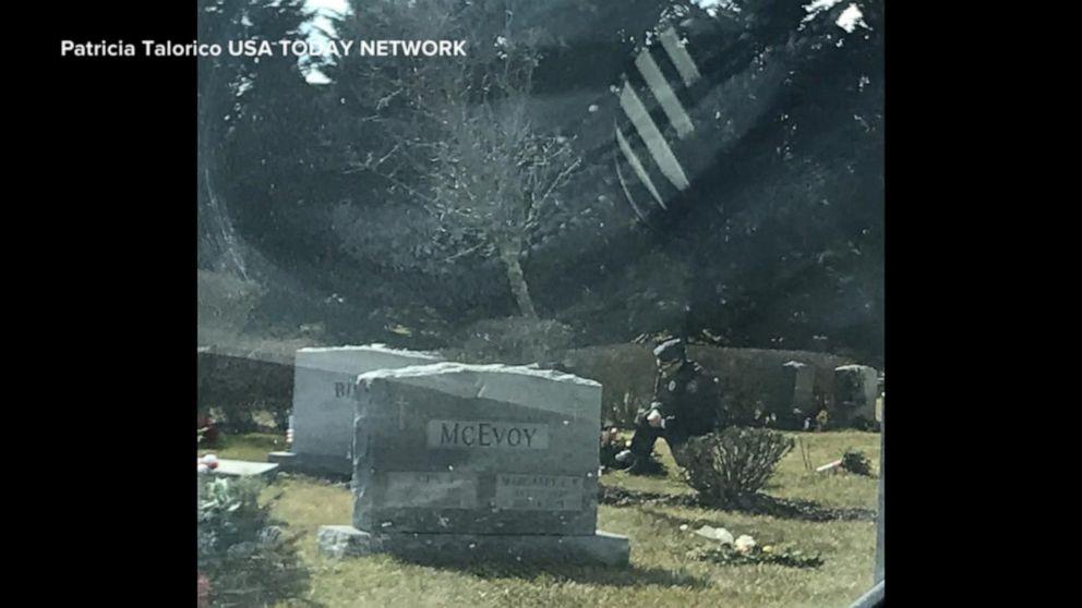 Man in blue uniform kneels at Beau Biden's grave
