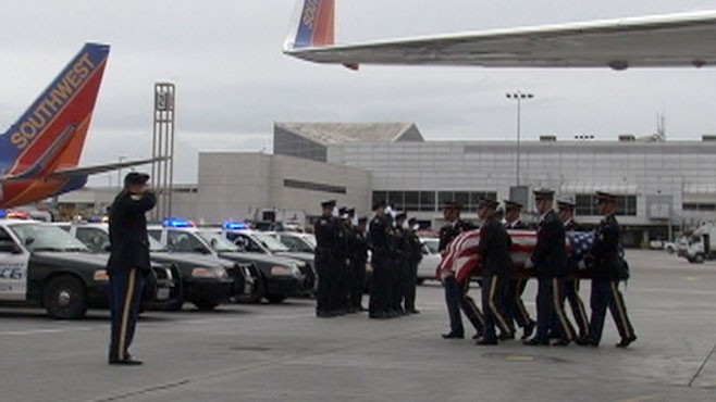 VIDEO: Police officer leads honor guards for war dead arriving at LAX.