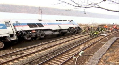 Commuter train on busy holiday weekend slips off tracks, rolls over, leaving at least four dead.
