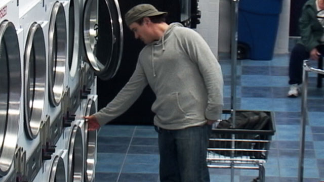 PHOTO a laundry thief who starts taking clothes from the machine the customer has been entrusted with and putting the ones he likes in a basket with all the other clothes hes taken.